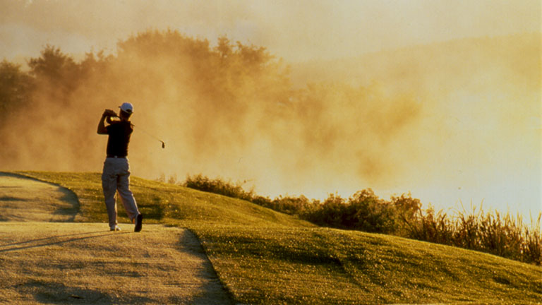 Golfer swinging at the edge of the fairway in morning fog.
