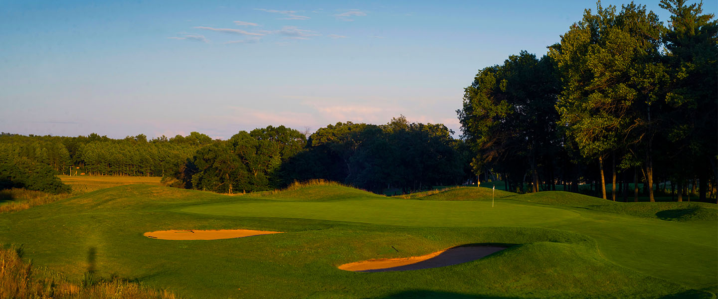 The green guarded by bunkers at sunset.