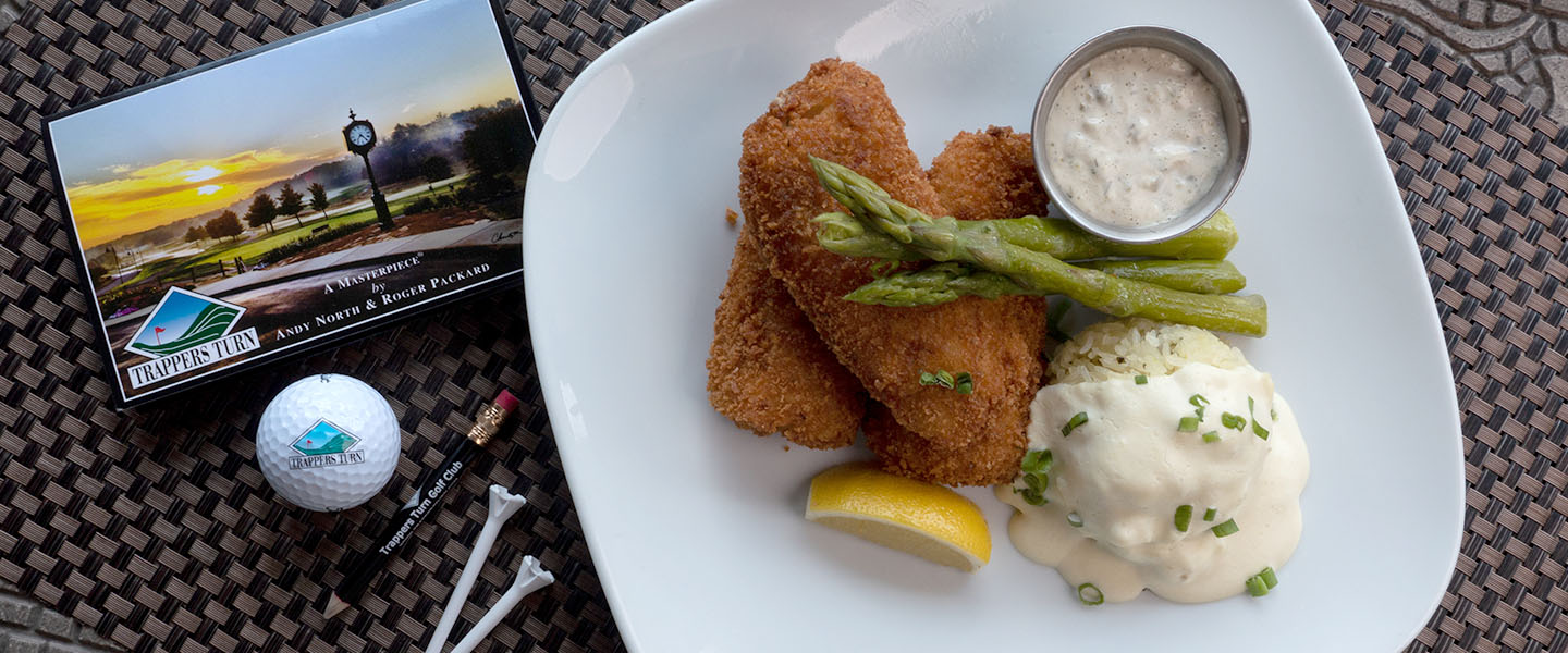 Plate of breaded and fried fish with asparagus and mashed potato, garnished with lemon.