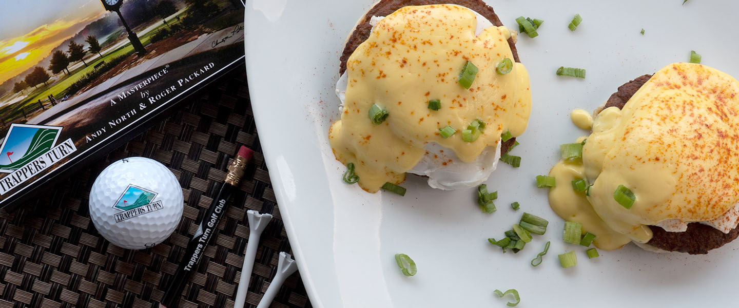 plate of Eggs Benedict garnished with scallion.