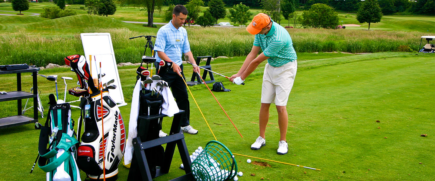 Golf Instructor assisting golfer with swing.