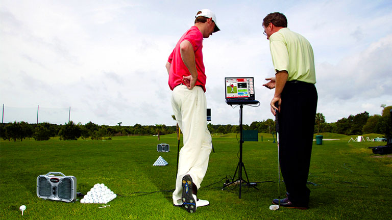 Trappers turn golf instructor with student analyzing his recorded swing at the practice facility