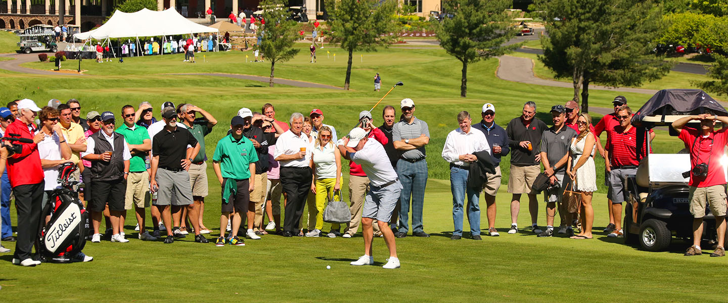 A male golfer about to drive, watched by a large group.
