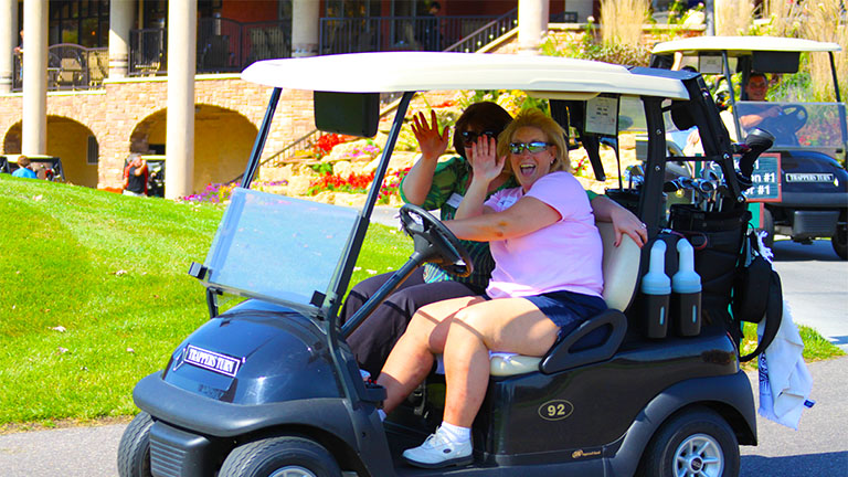 Two women driving a golf cart, headed to the course, waving and smiling