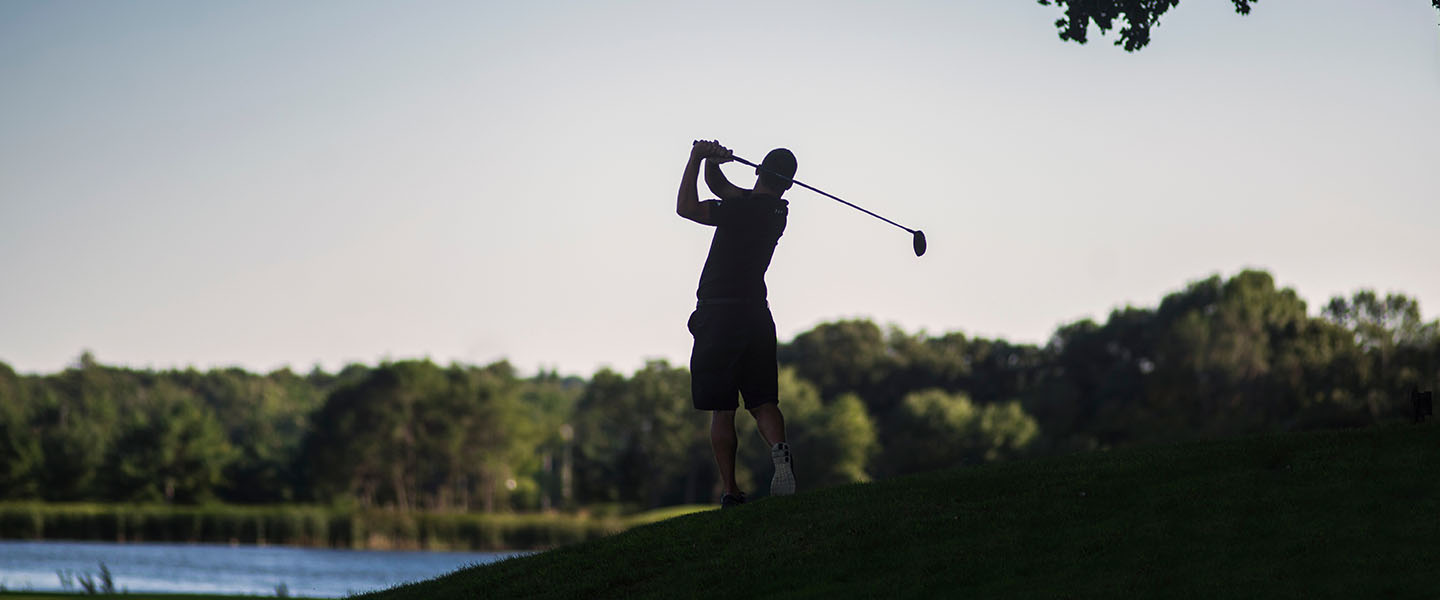 Silhouette of a golfer swinging.