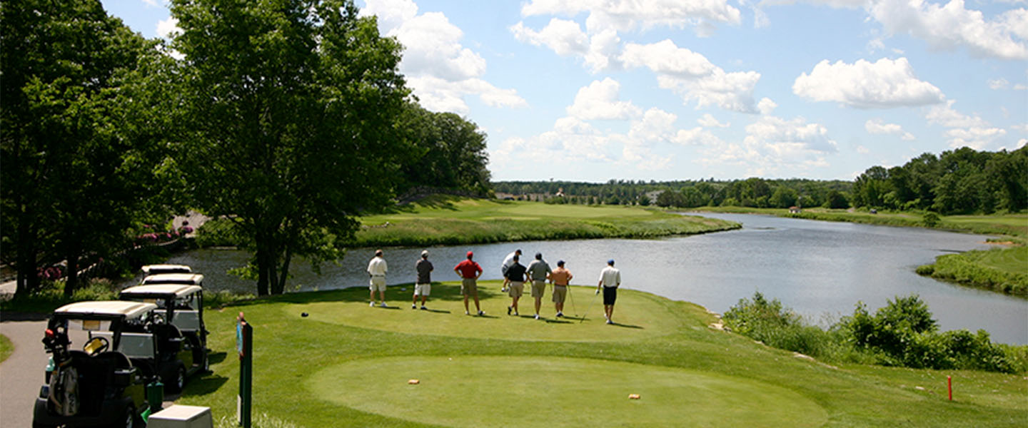 Group of golfers teeing off over Mystic Lake.