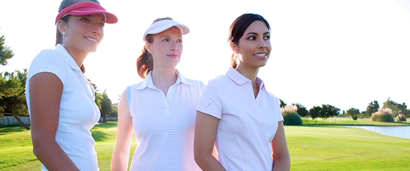 Three female golfers on the fairway.