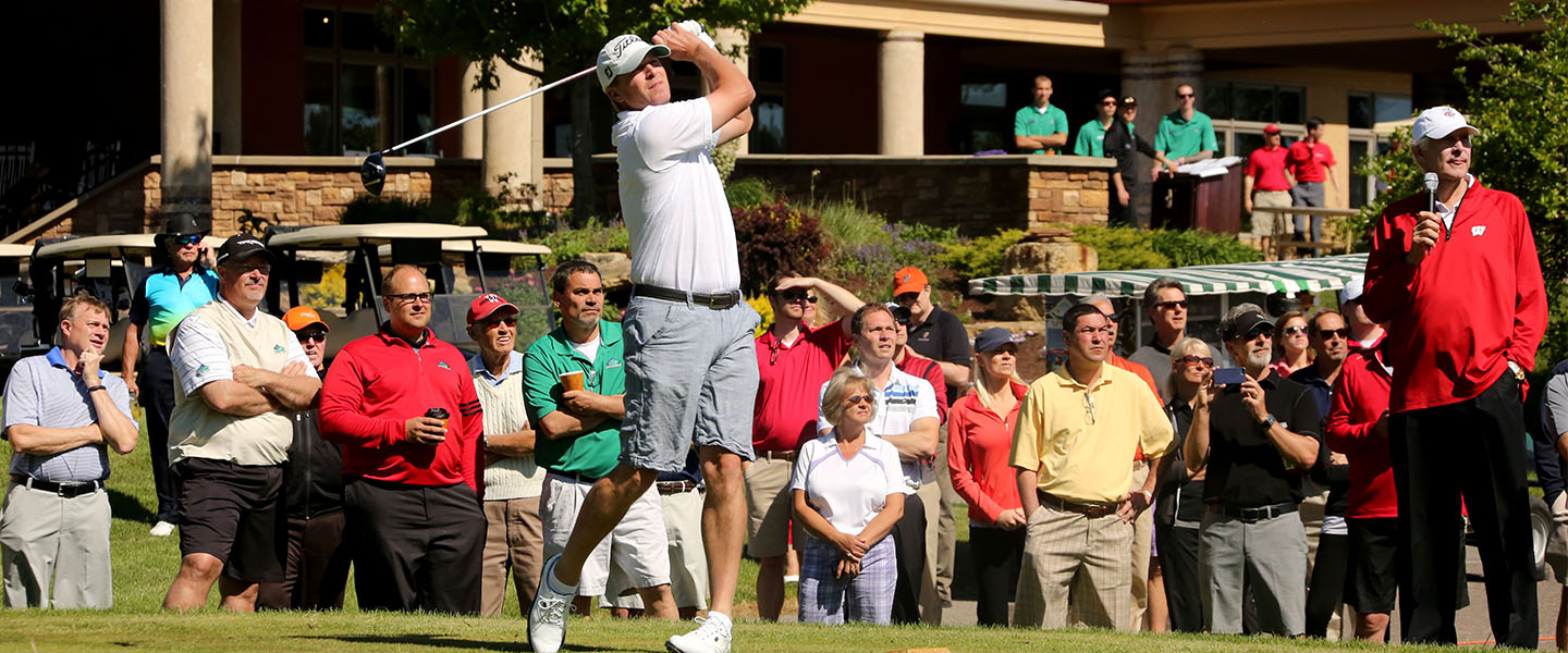 Male golfer swinging as Andy North commentates and spectators watch.