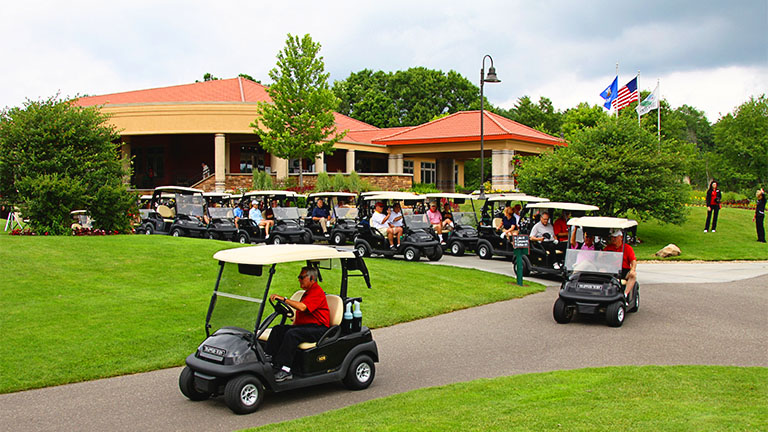 Train of golf carts leaving the clubhouse, heading toward the course during a golf outing