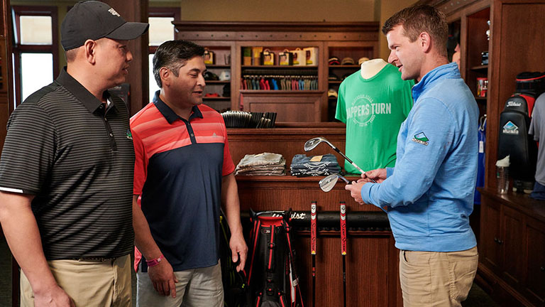 Trappers Turn golf shop staff assists two shoppers in choosing a club
